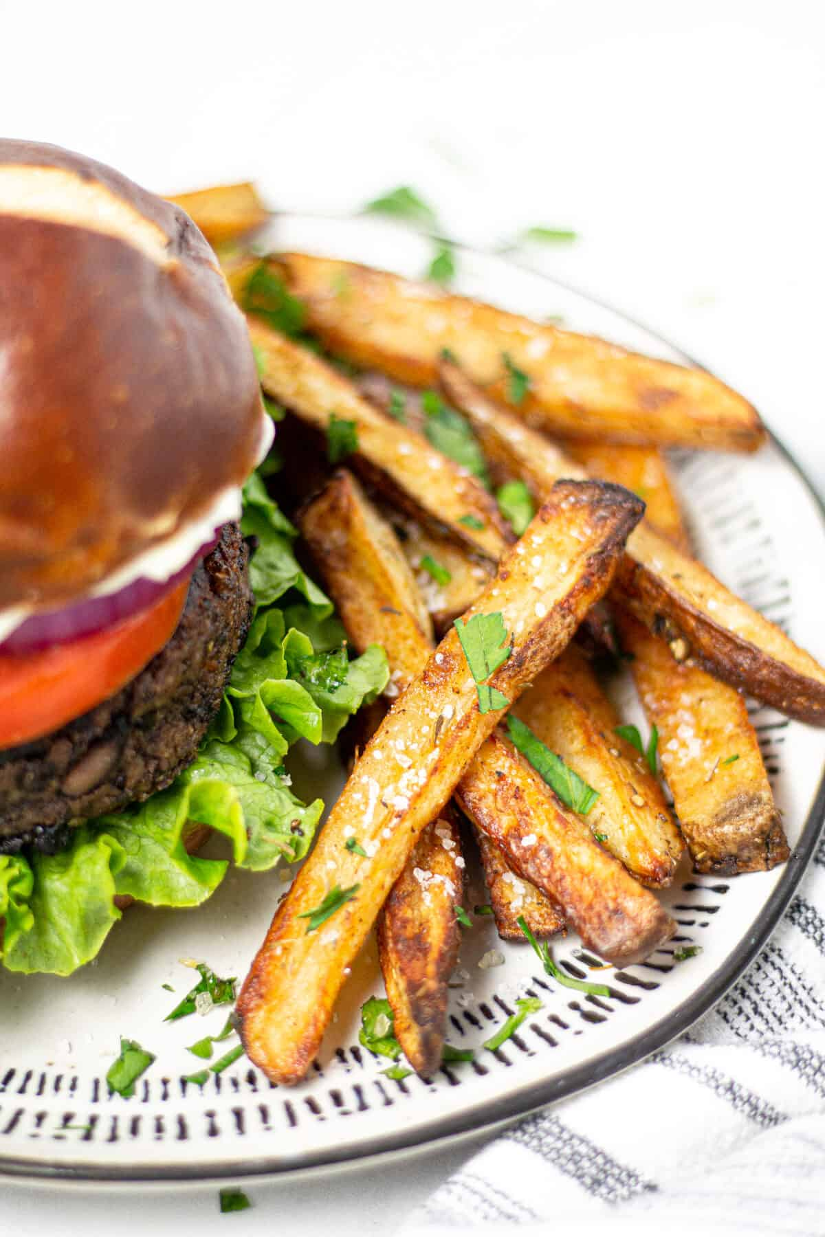 Plate with a black bean burger and baked french fries on it
