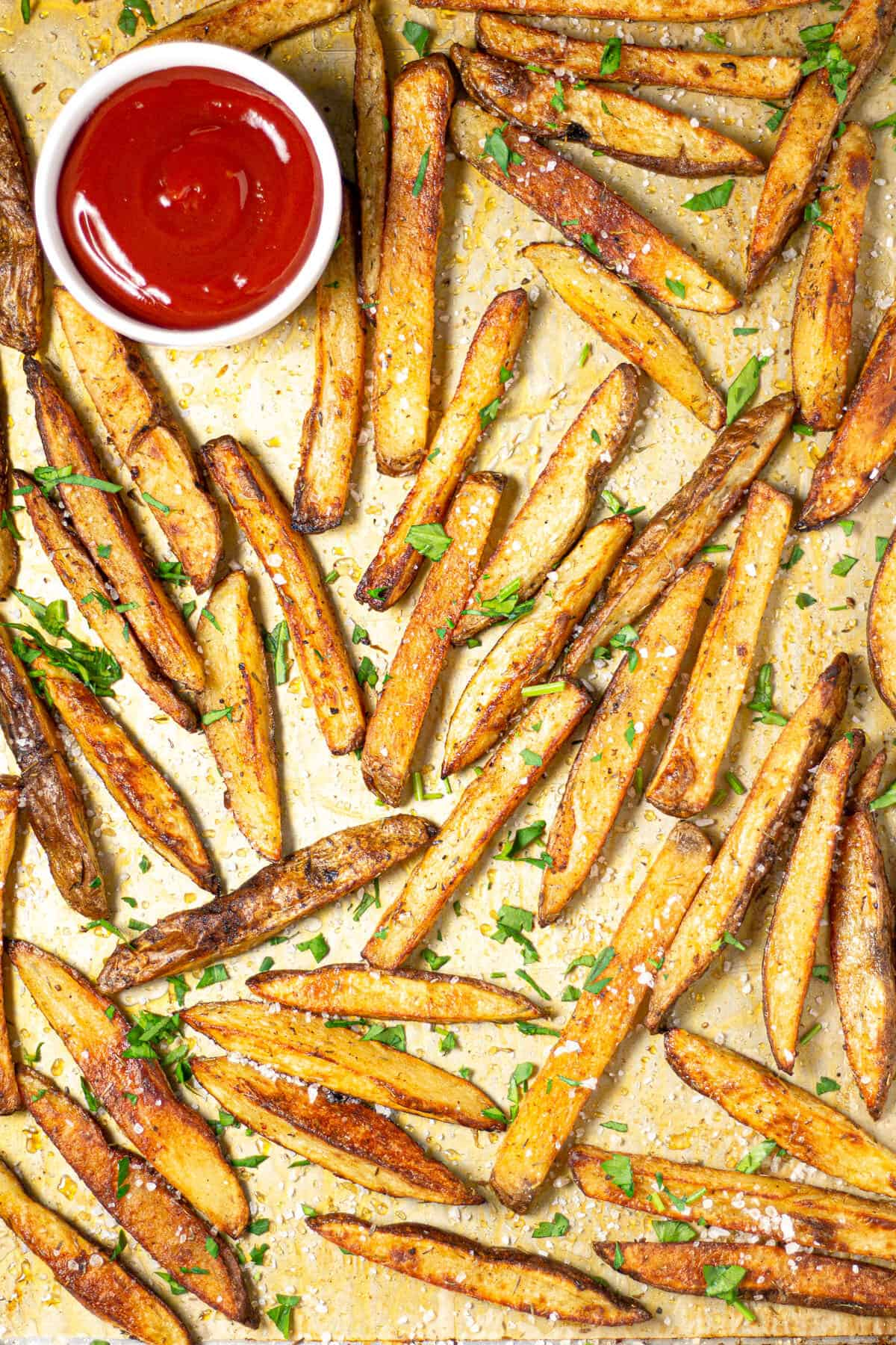Parchment lined baking sheet with freshly baked French fries and a small bowl of ketchup