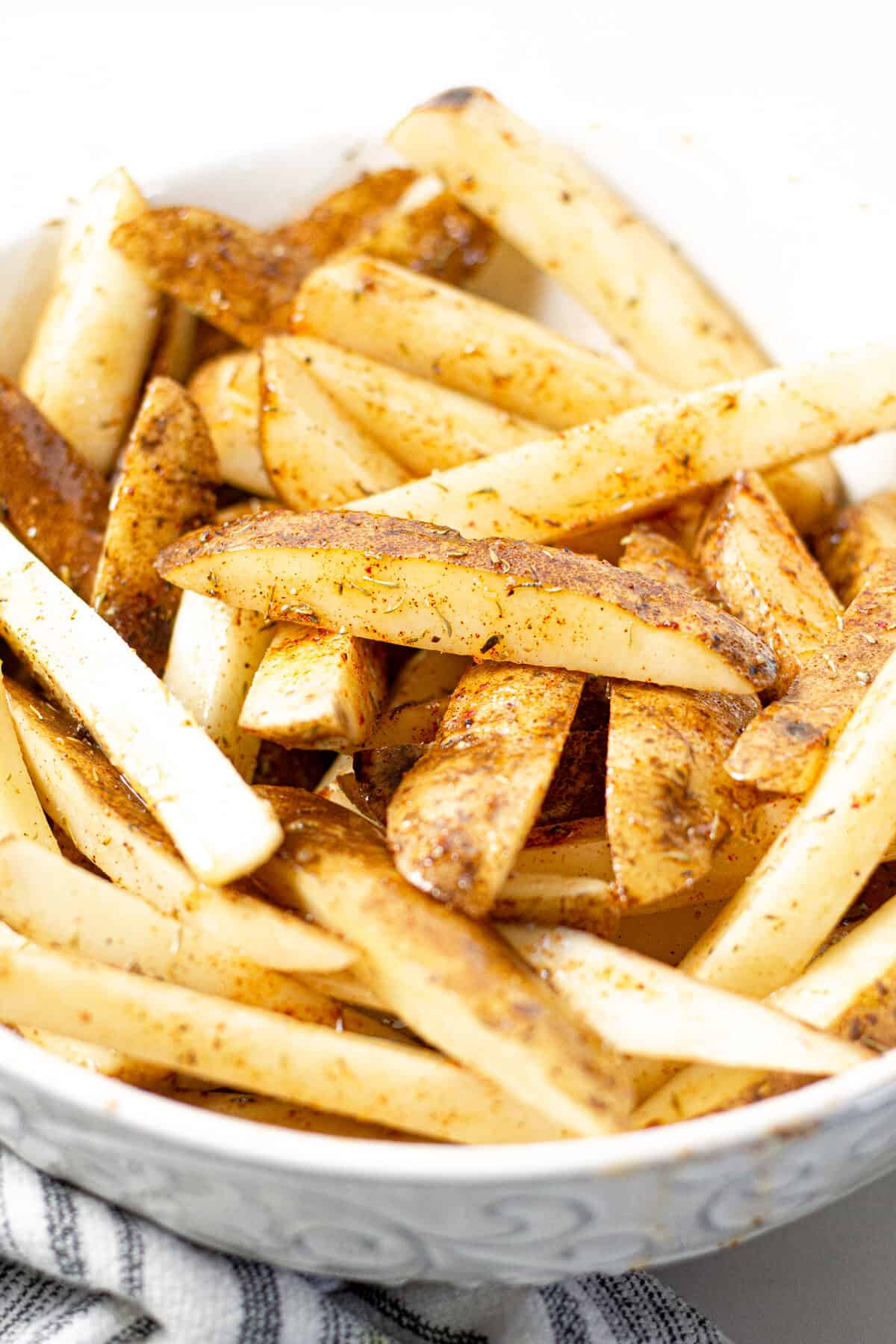 White bowl filled with fresh cut French fries tossed with seasonings