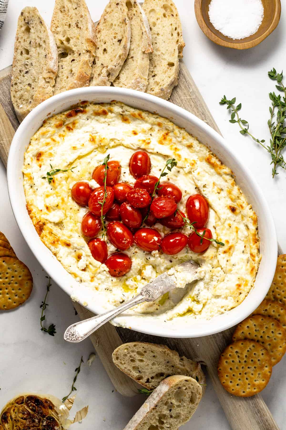 Overshot shot of baked goat cheese dip garnished with roasted tomatoes and fresh thyme