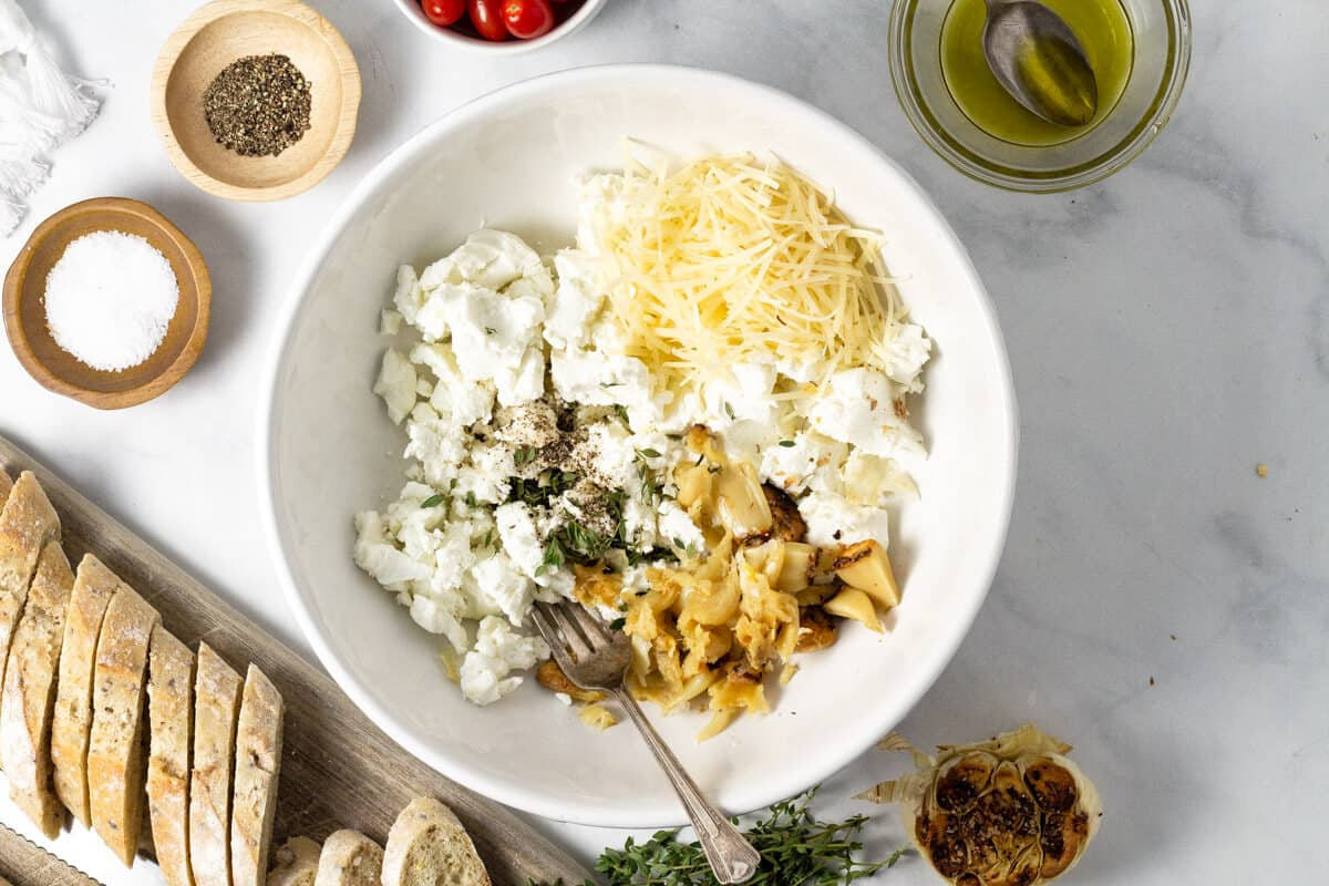 Large white bowl filled with ingredients to make roasted garlic goat cheese dip