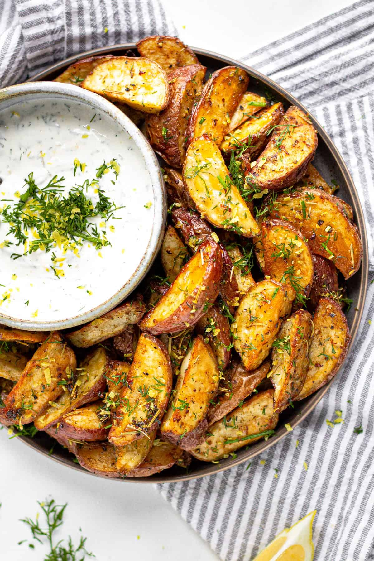 Overhead shot of plate filled with Greek Potato Wedges served with yogurt sauce