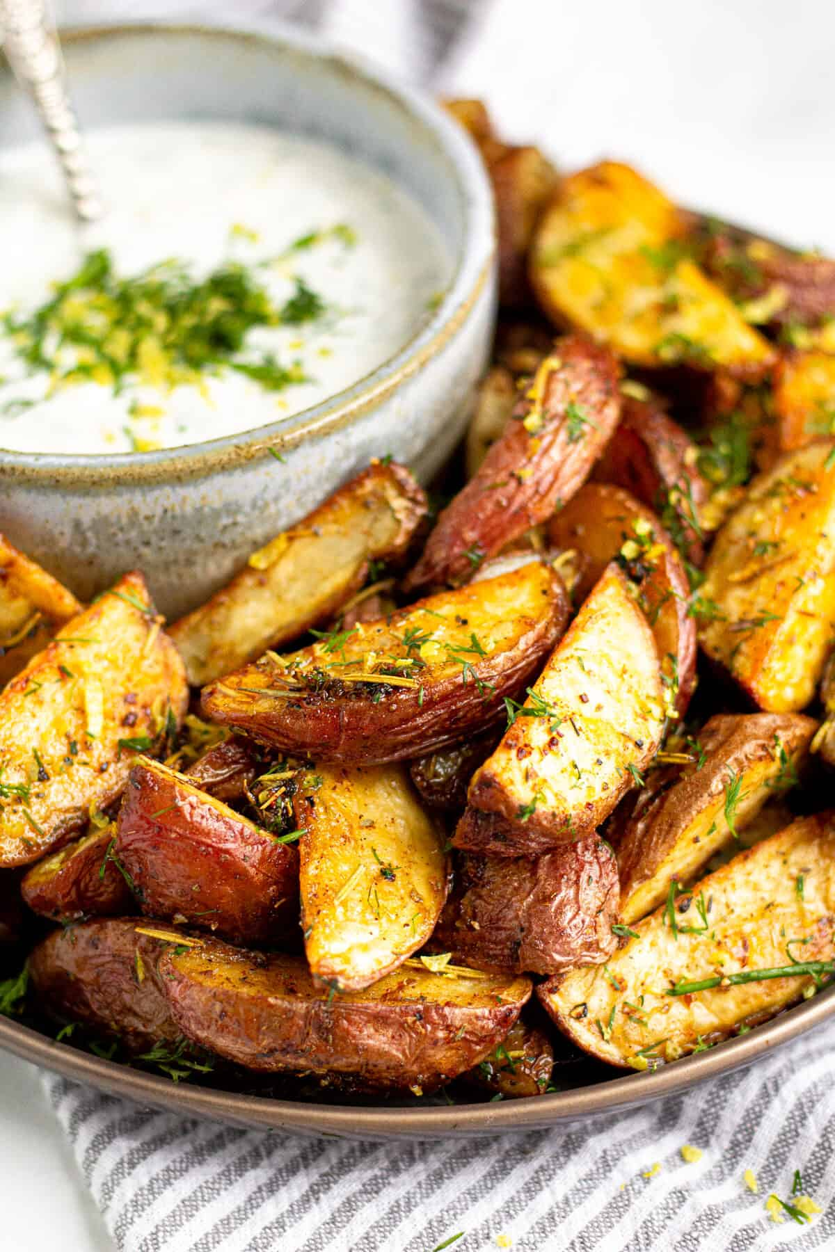 Close up shot of a plate filled with Greek potato wedges and yogurt sauce
