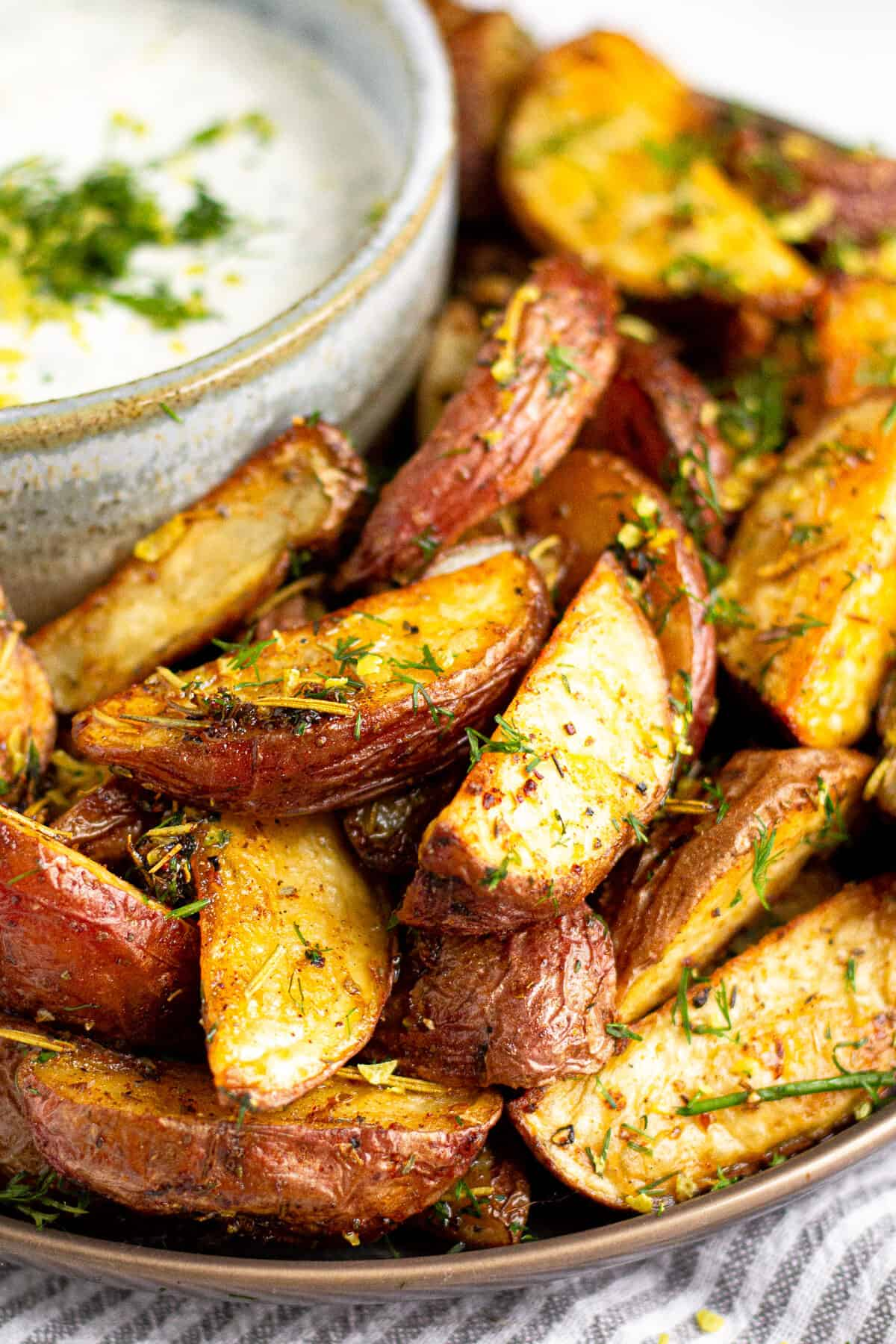 Close up shot of plate filled with Greek Potato Wedges served with yogurt sauce