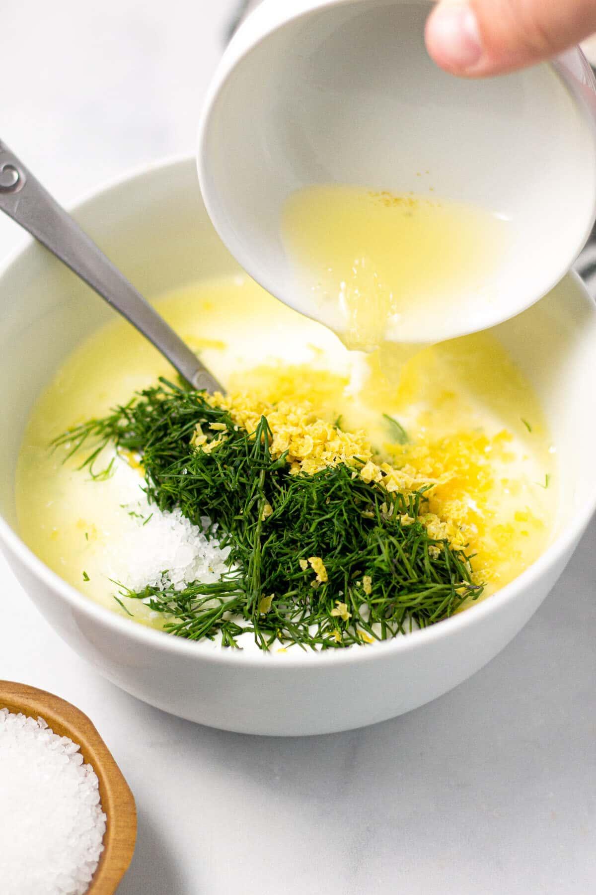 White bowl filled with ingredients to make Greek yogurt sauce