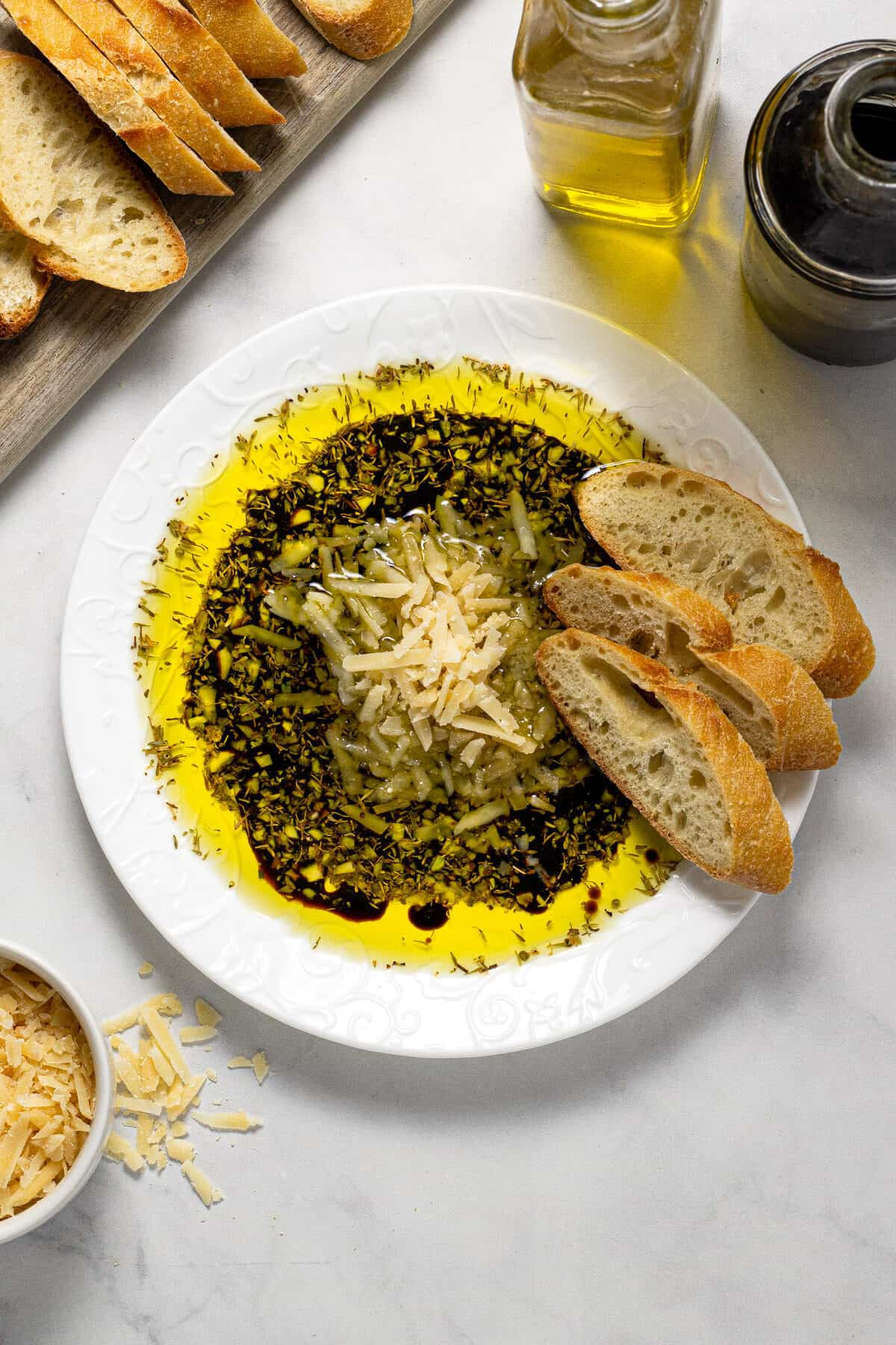 Overhead shot of a plate filled with olive oil and balsamic vinegar dip with Parmesan cheese and herbs