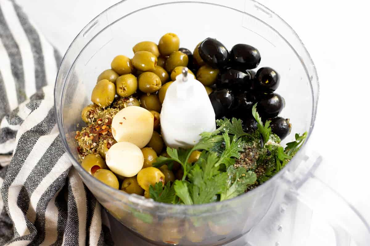 Food processor filled with ingredients to make olive tapenade
