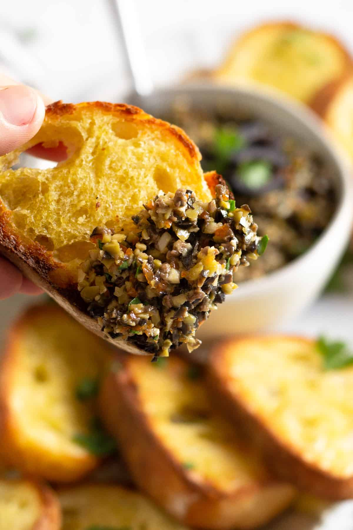 Close up shot of a crostini with a big scoop of olive tapenade on it