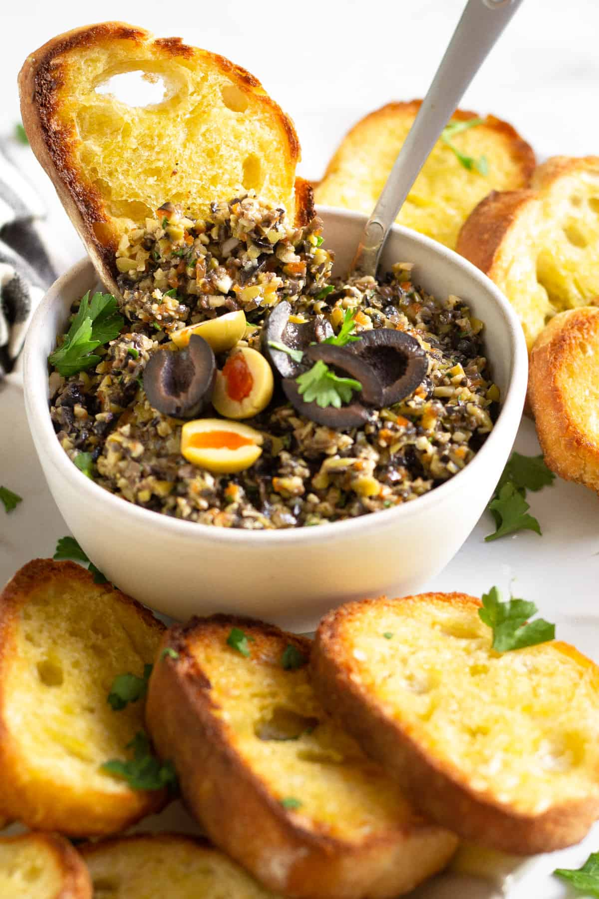 Close up shot of a white bowl filled with olive tapenade garnished with fresh parsley