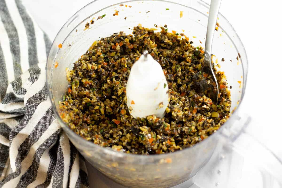 Food processor filled with homemade olive tapenade