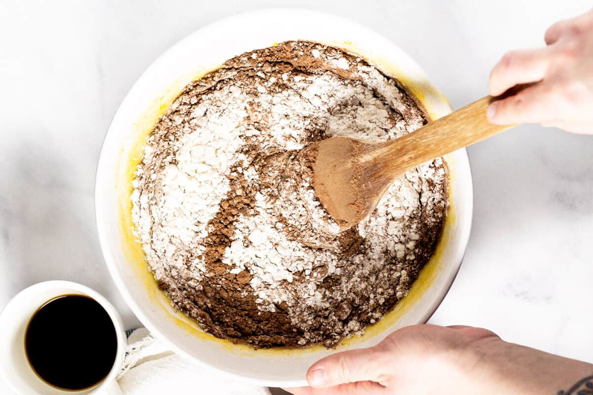 Large white bowl with brownie batter in it and a hand stirring the batter with a wooden spoon