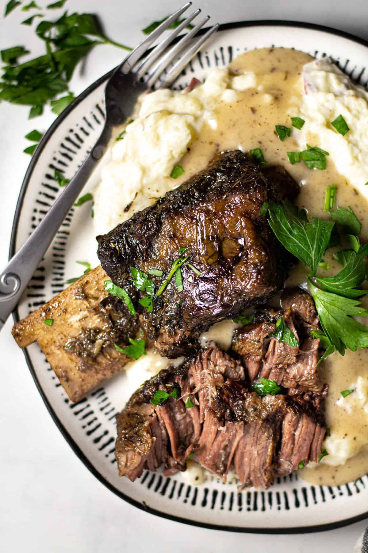 Overhead shot of a plate filled with short ribs and homemade mashed potatoes garnished with parsley