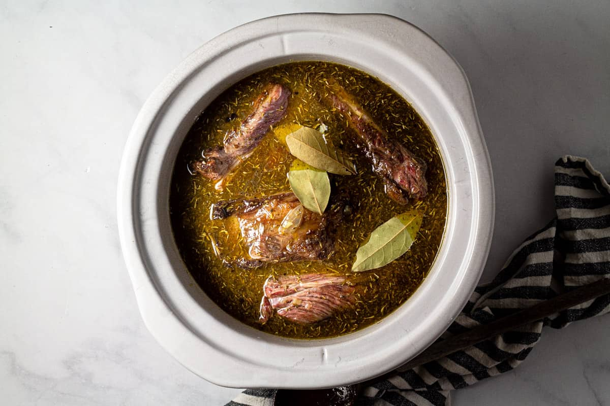 Large crock pot insert filled with seared short ribs and beer