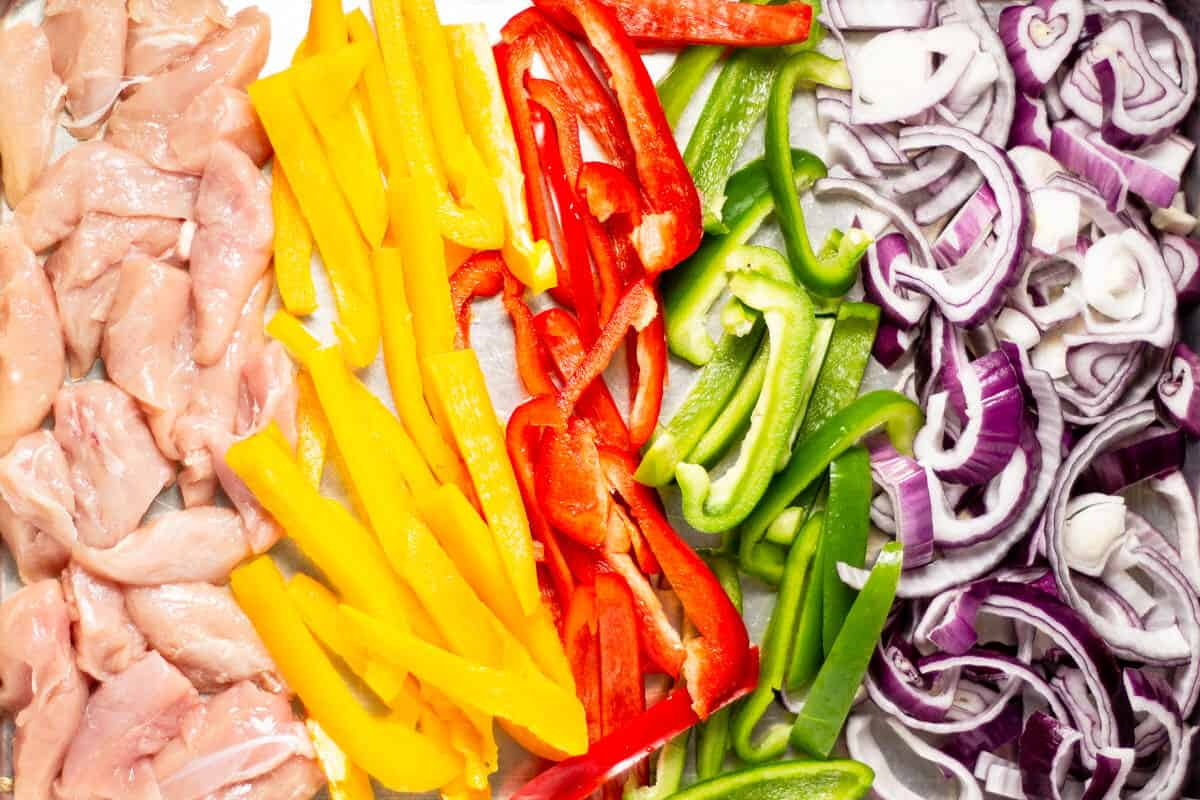 Sheet pan filled with chicken peppers and onions for sheet pan fajitas