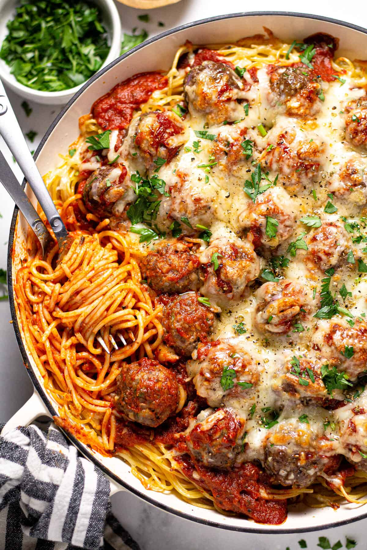Overhead shot of a pan filled with baked spaghetti and meatballs garnished with fresh parsley