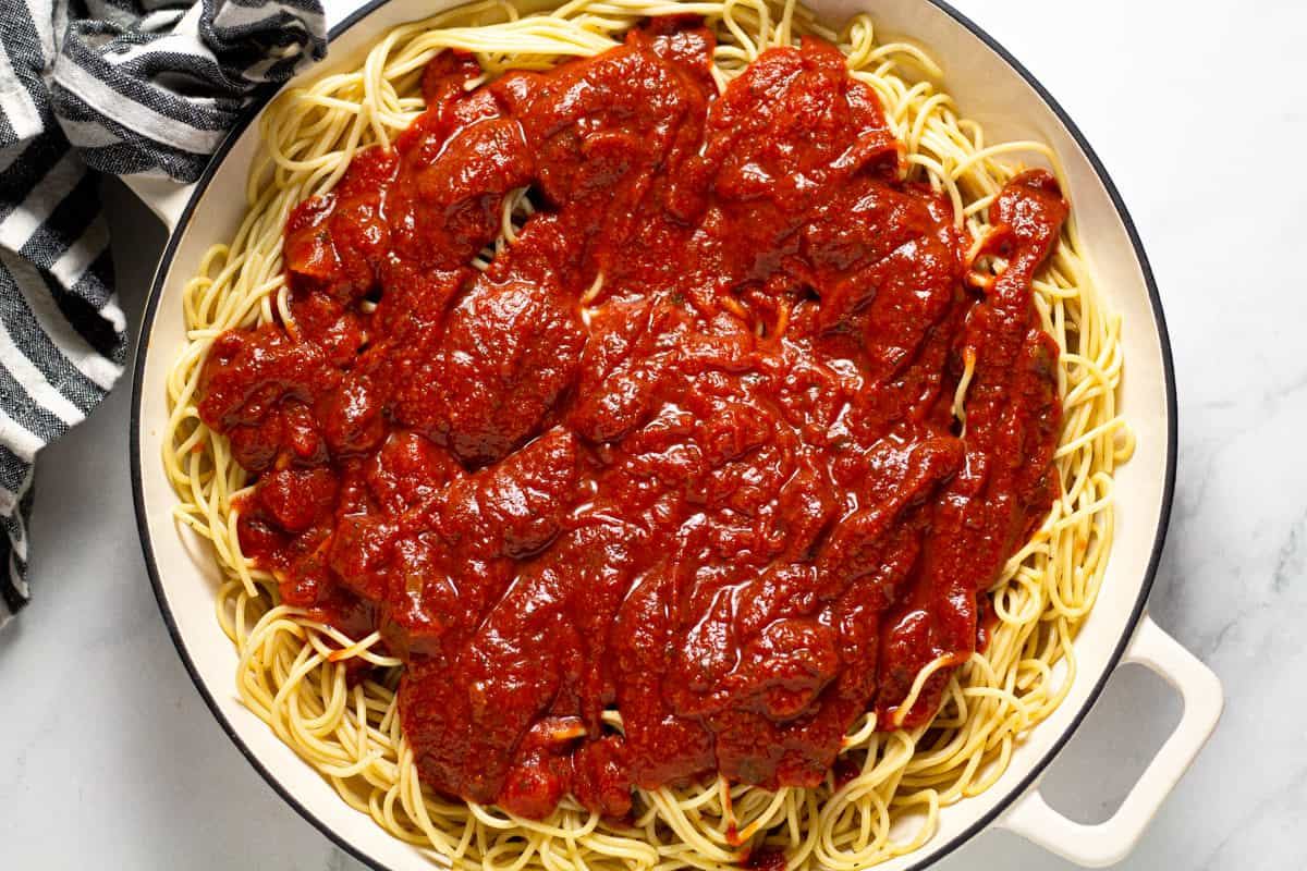 Large white pan filled with spaghetti and red pasta sauce