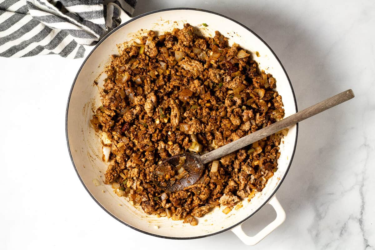 Overhead shot of a white pan filled with ground turkey and chili spices