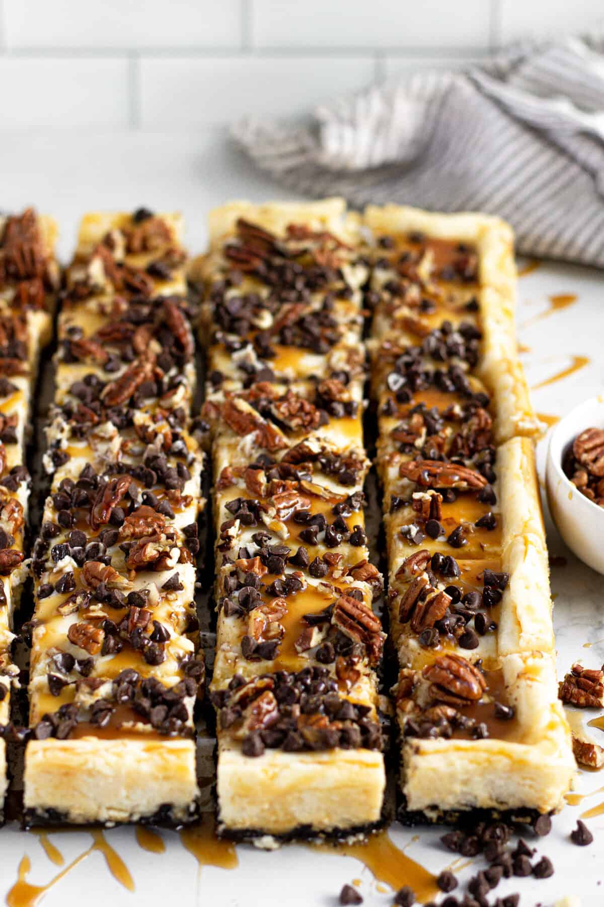 Close up shot of turtle cheesecake bars with chocolate chips and caramel