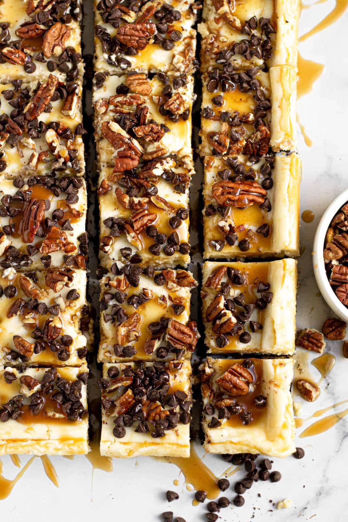 Close up shot of turtle cheesecake bars topped with chocolate and caramel
