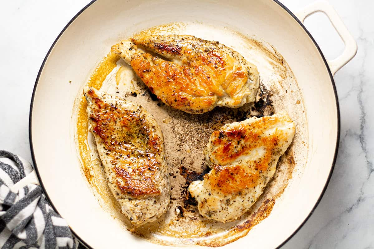 Large white pan filled with sauteed chicken breast