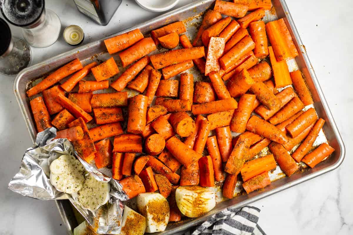 Baking sheet filled with seasoned carrots onions and garlic