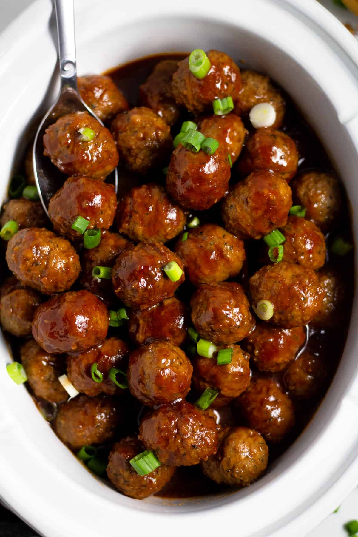 Overhead shot of a white crock pot insert filled with bourbon whiskey meatballs