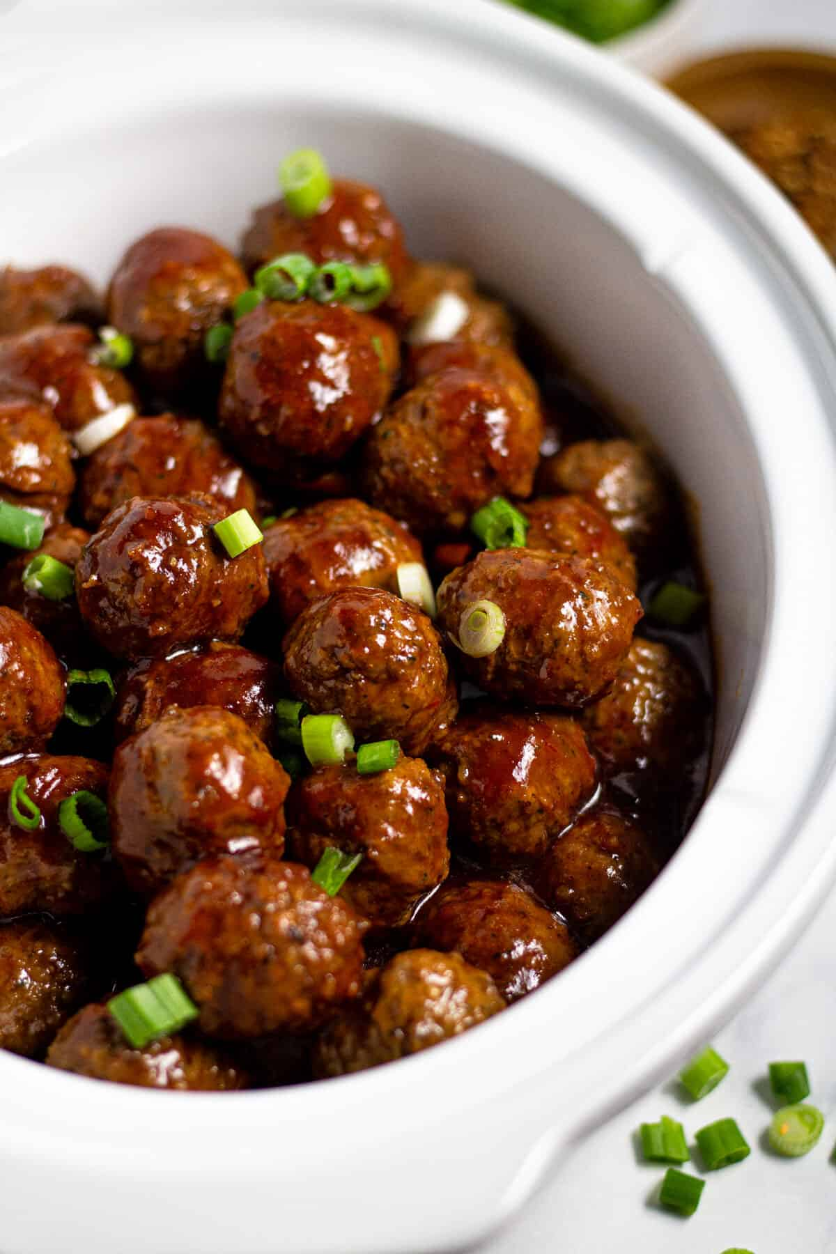 Close up shot of a white crock pot insert filled with bourbon whiskey meatballs