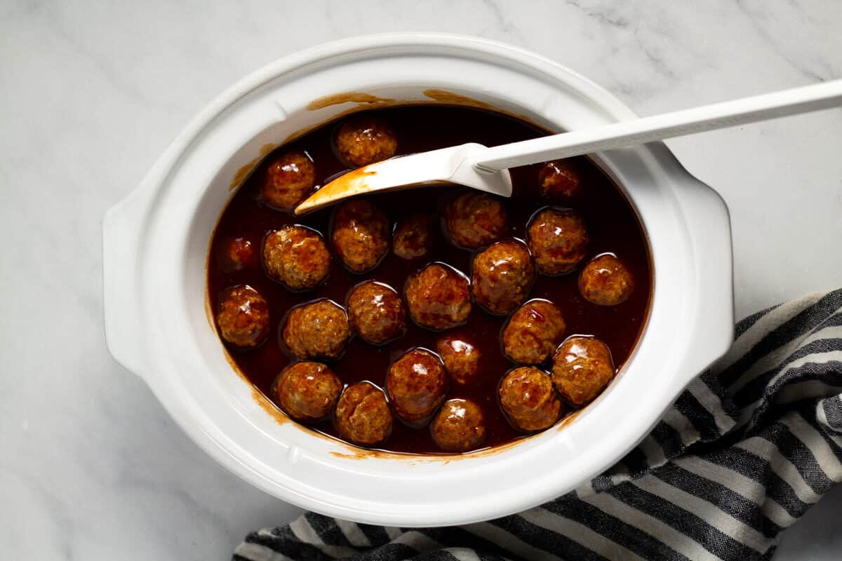Overhead shot of an oval white crock pot insert filled with whiskey bourbon barbecue sauce and frozen meatballs