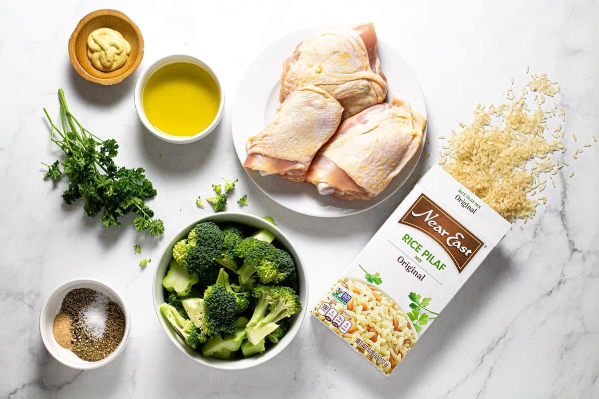 Gray marble countertop with ingredients to make roasted chicken thighs with rice and broccoli