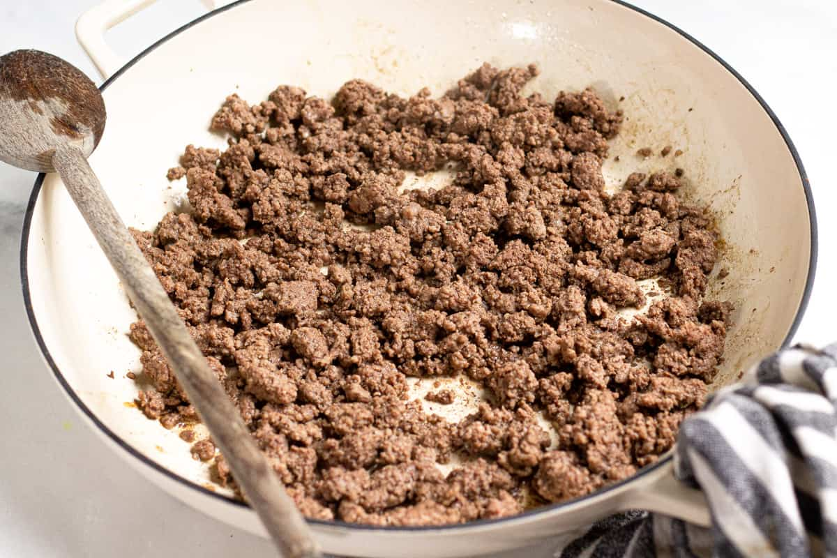 Large saute pan filled with cooked ground beef