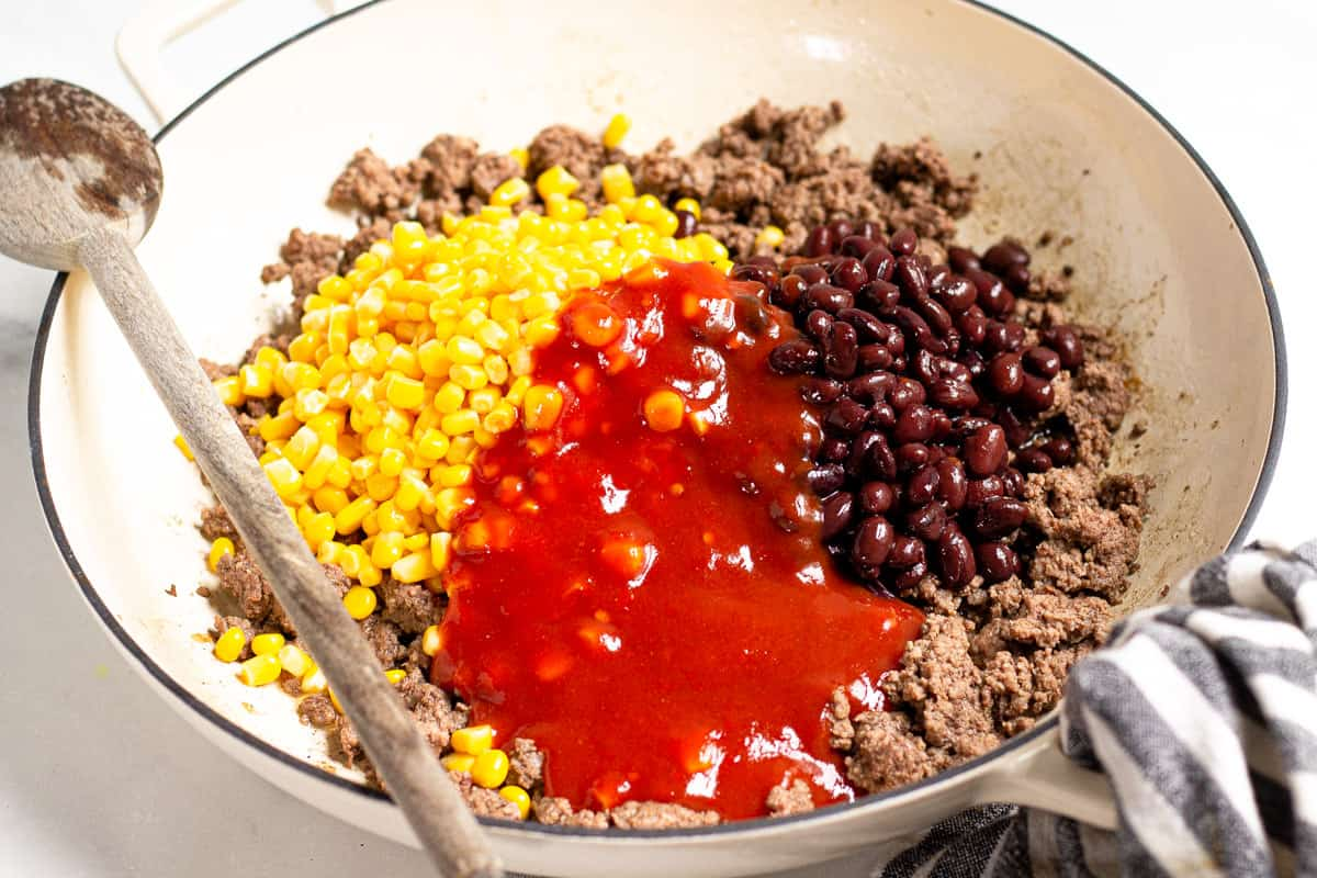 Large saute pan filled with cooked ground beef corn black beans and taco sauce