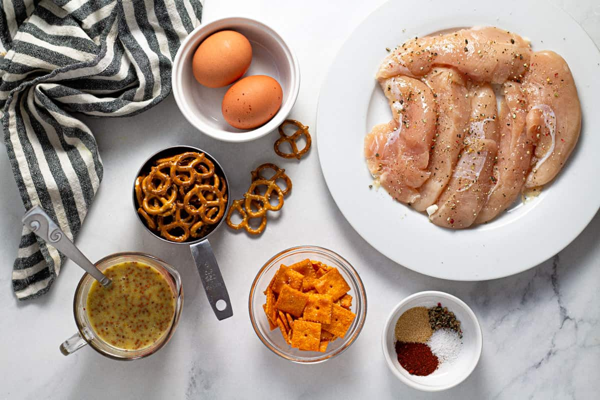 Overhead shot of ingredients to make chicken tenders laid out on a white marble counter top