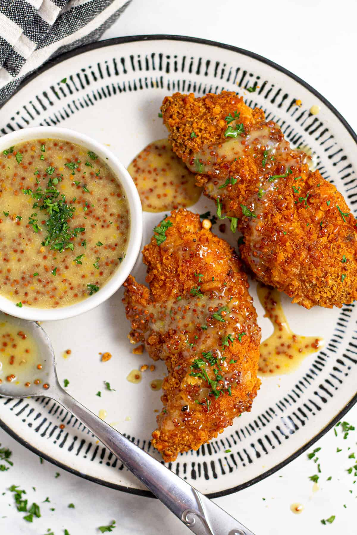 Overhead shot of baked chicken tenders on a white plate garnished with fresh parsley