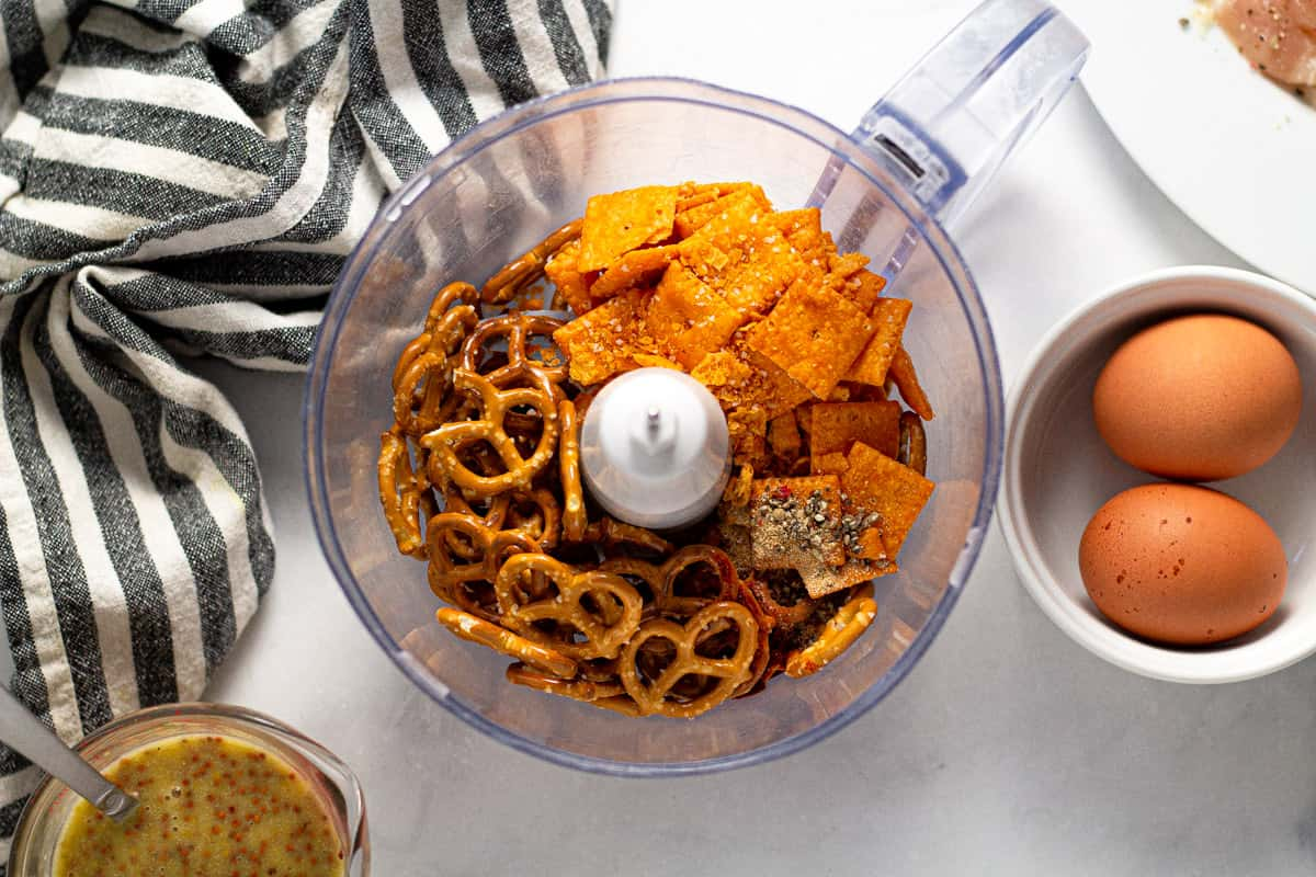 Food processor filled with pretzels and cheez its