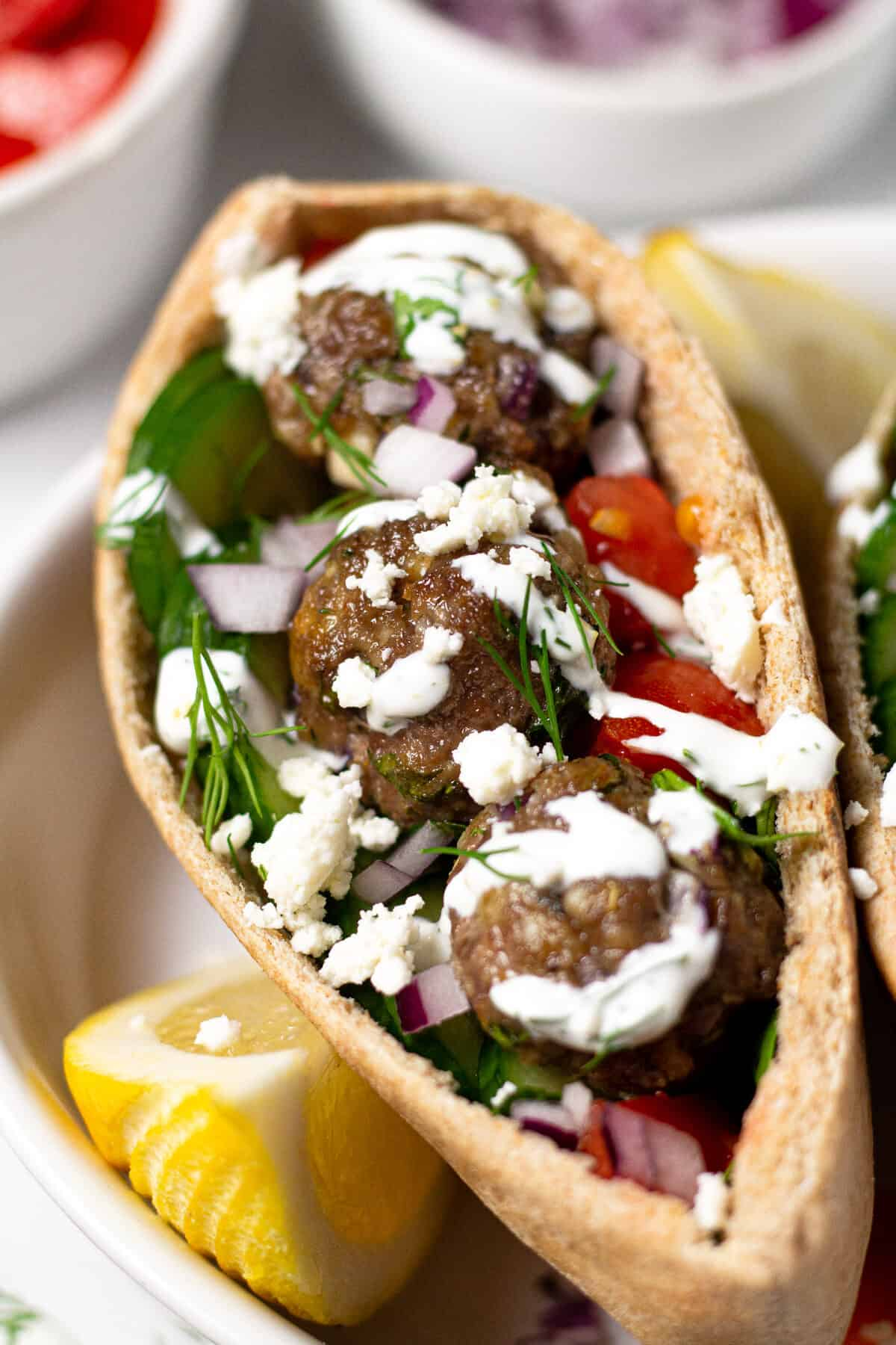 Close up shot of a Greek meatball gyro with yogurt sauce and fresh dill