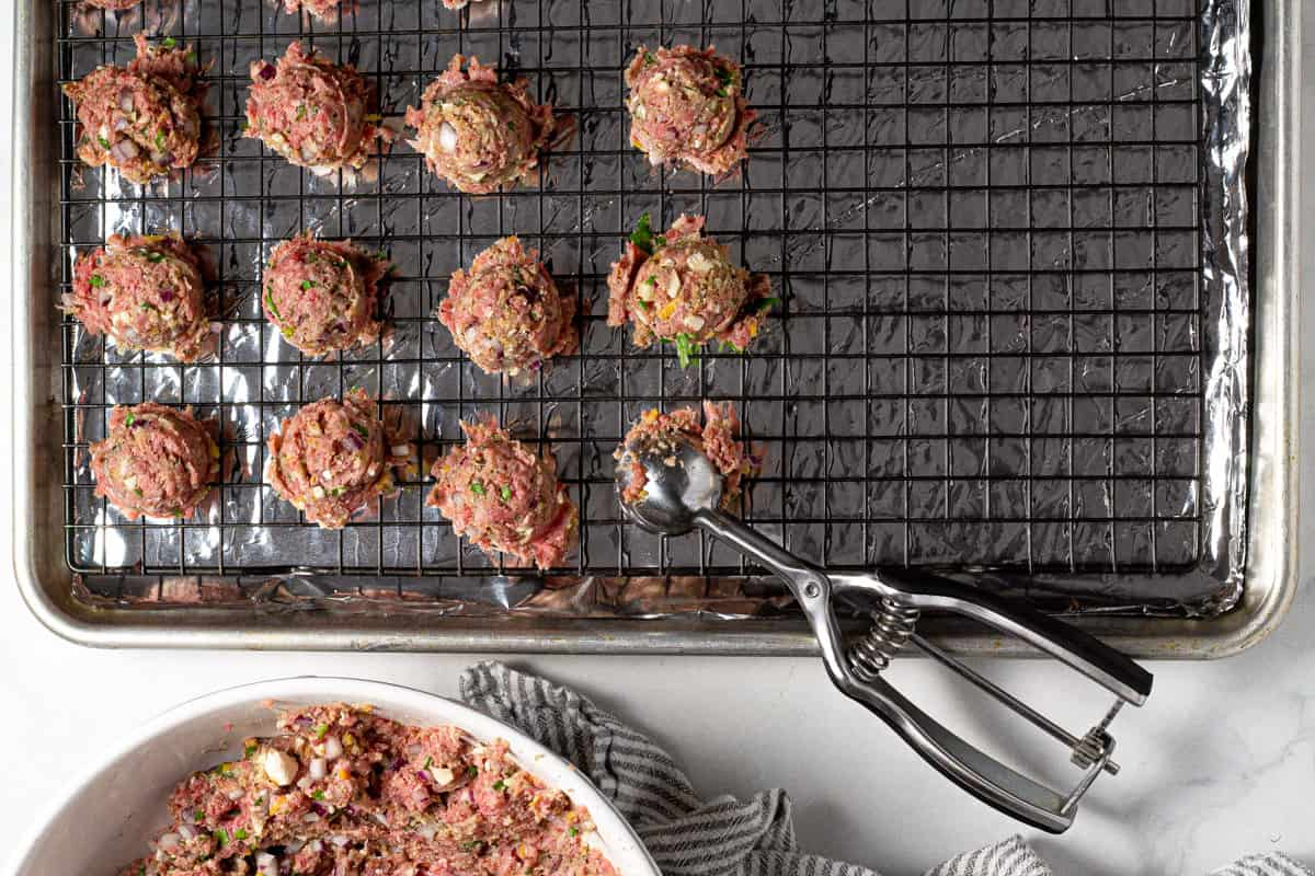 A cookie scoop scooping meatballs onto a baking sheet