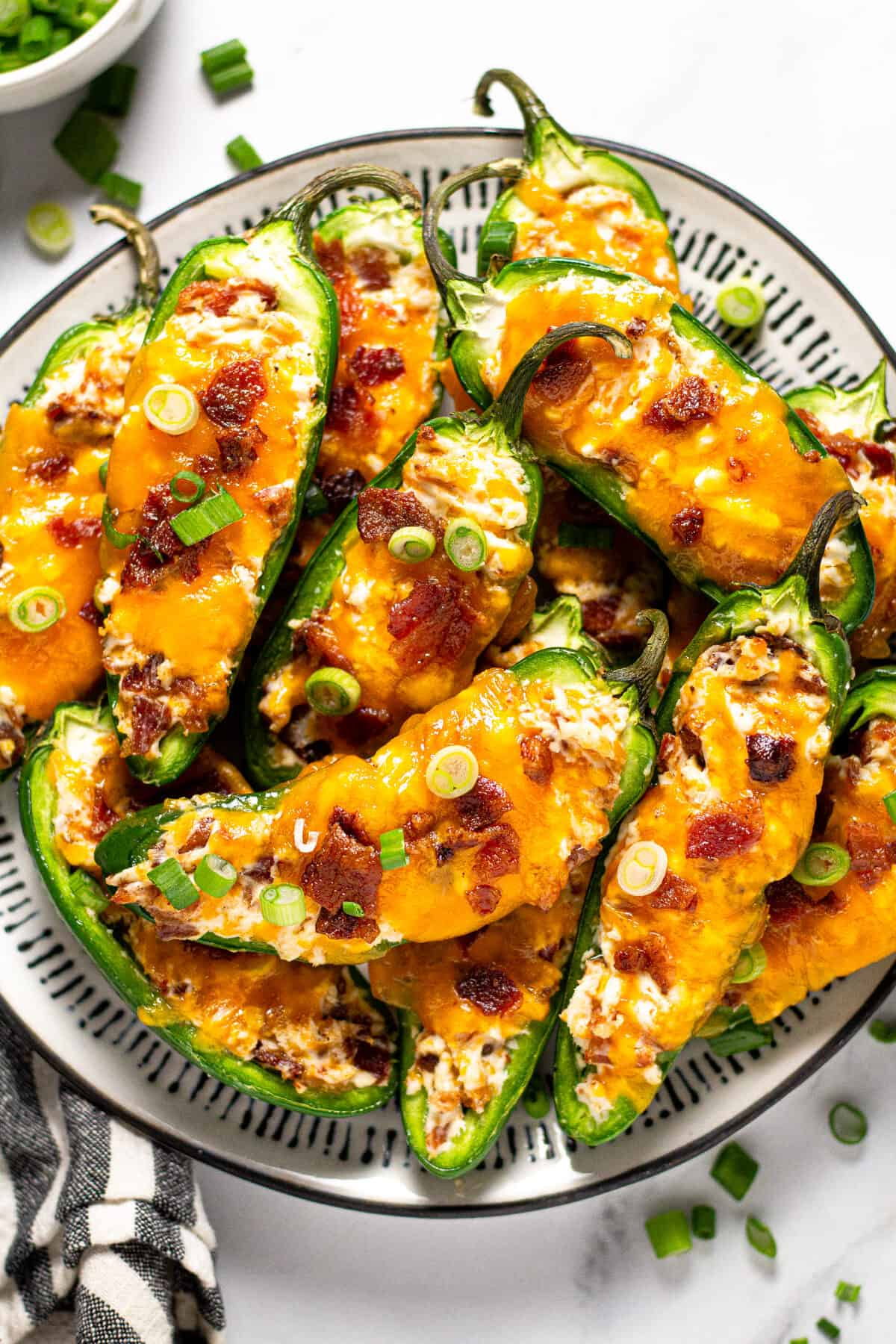Black and white plate filled with baked jalapeno poppers garnished with green onion