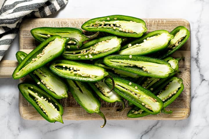 Wooden cutting board filled with jalapenos sliced in half lengthwise