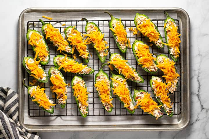 An overhead shot of a cooling rack filled with jalapeno poppers