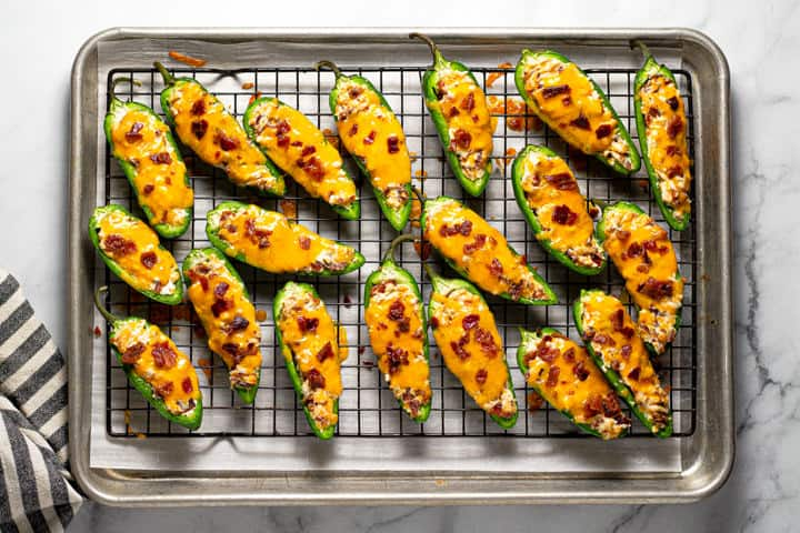 An overhead shot of a cooling rack filled with baked jalapeno poppers