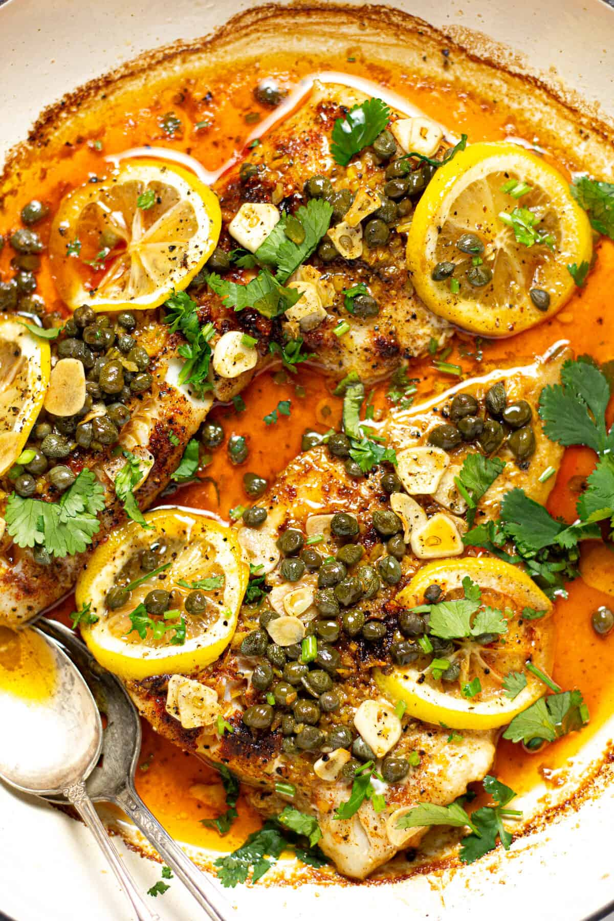 Overhead shot of a pot filled with baked Mediterranean cod garnished with fresh cilantro