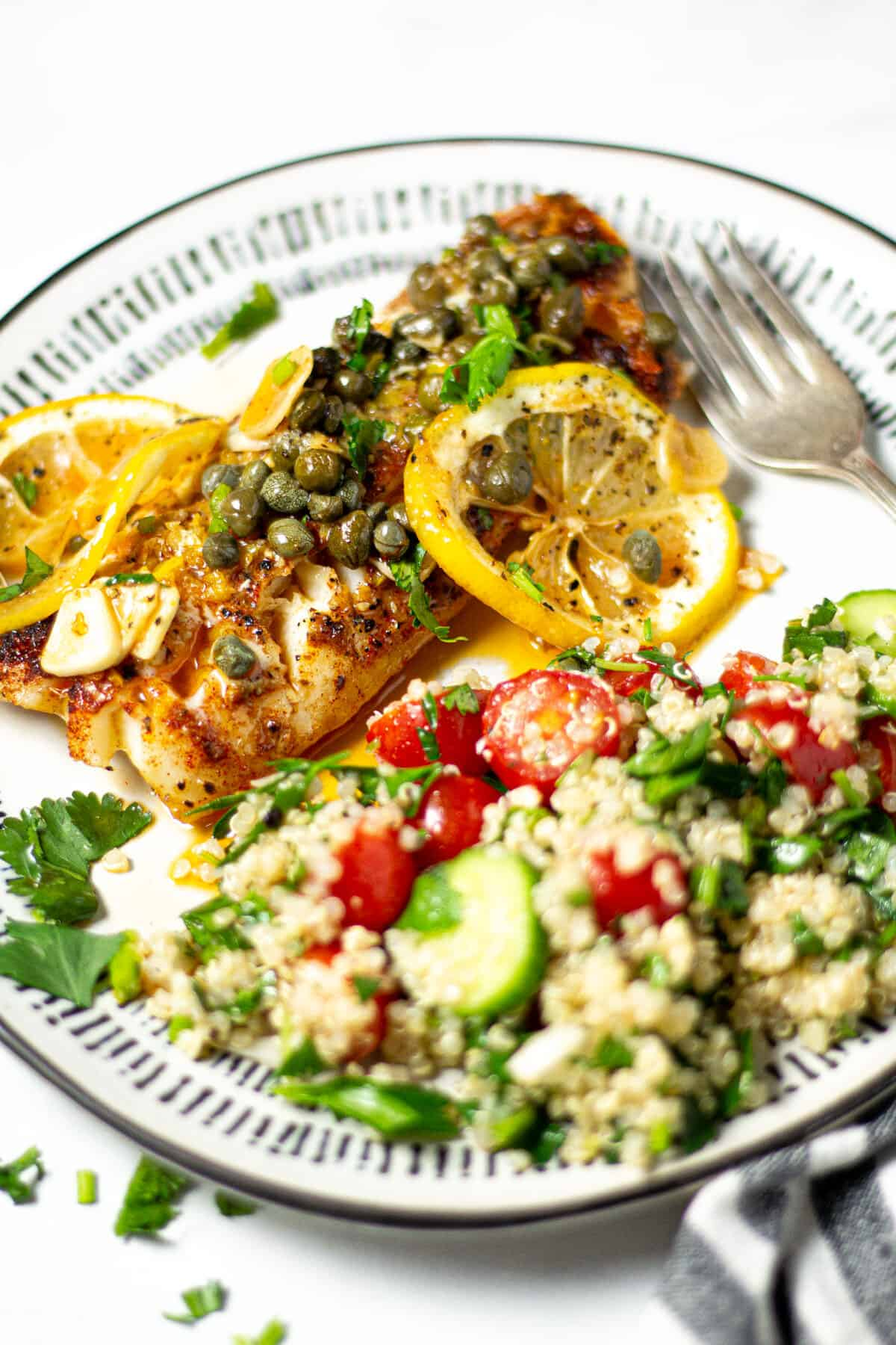 A plate filled with quinoa tabbouleh and Mediterranean cod garnished with fresh parsley