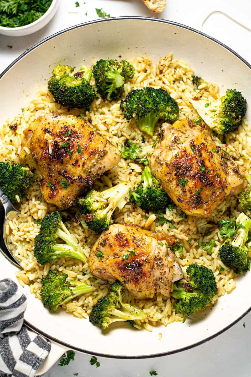 Overhead shot of a pan filled with rice pilaf broccoli and roasted chicken thighs