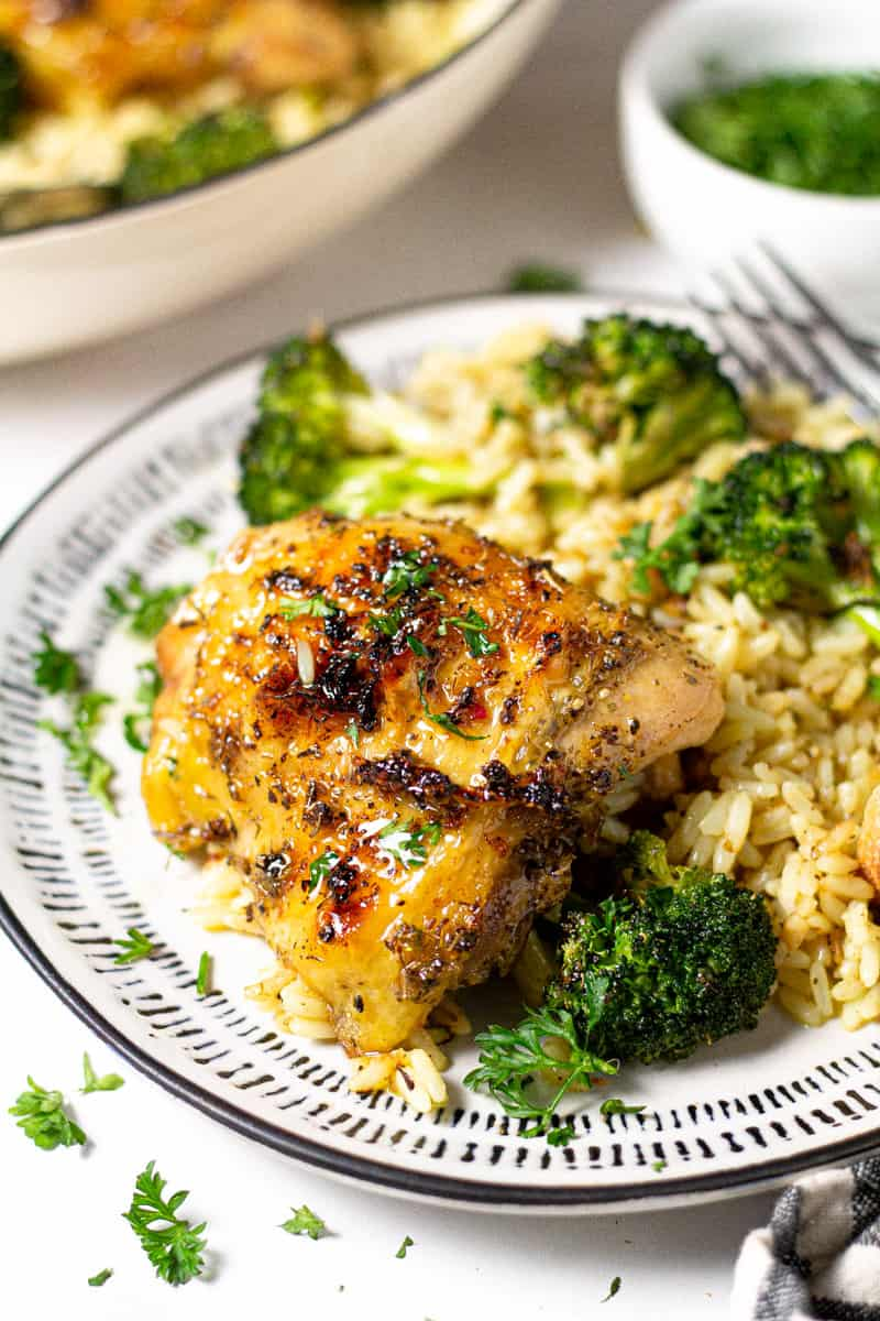 Close up shot of a roasted chicken thigh on a white plate with rice pilaf and broccoli