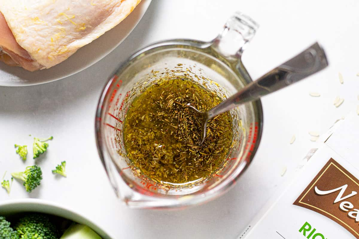 Measuring cup filled with a chicken marinade of olive oil and dried herbs