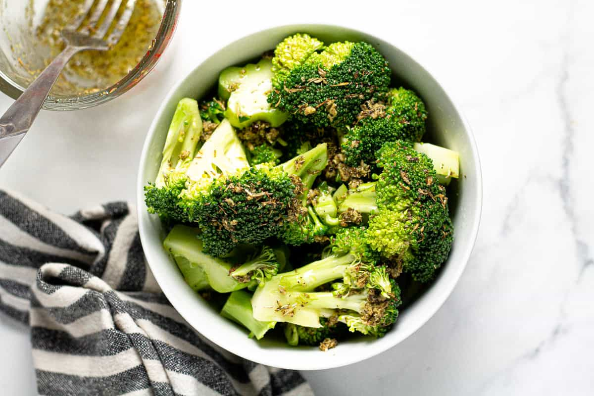 White bowl filled with broccoli tossed in olive oil and dried herbs
