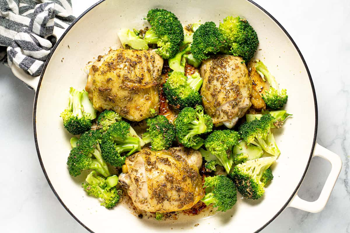 Large white pan filled with chicken thighs and broccoli