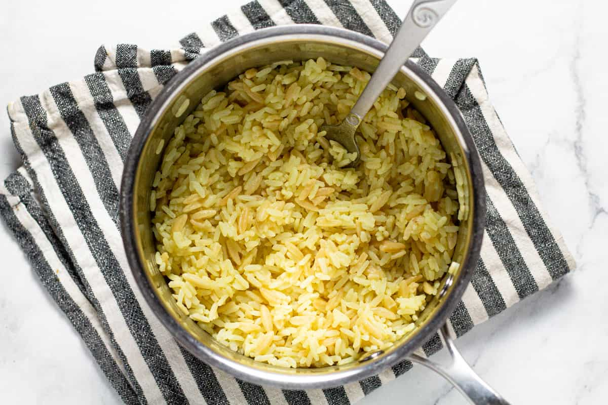Small sauce pan filled with cooked rice pilaf on a lined kitchen towel