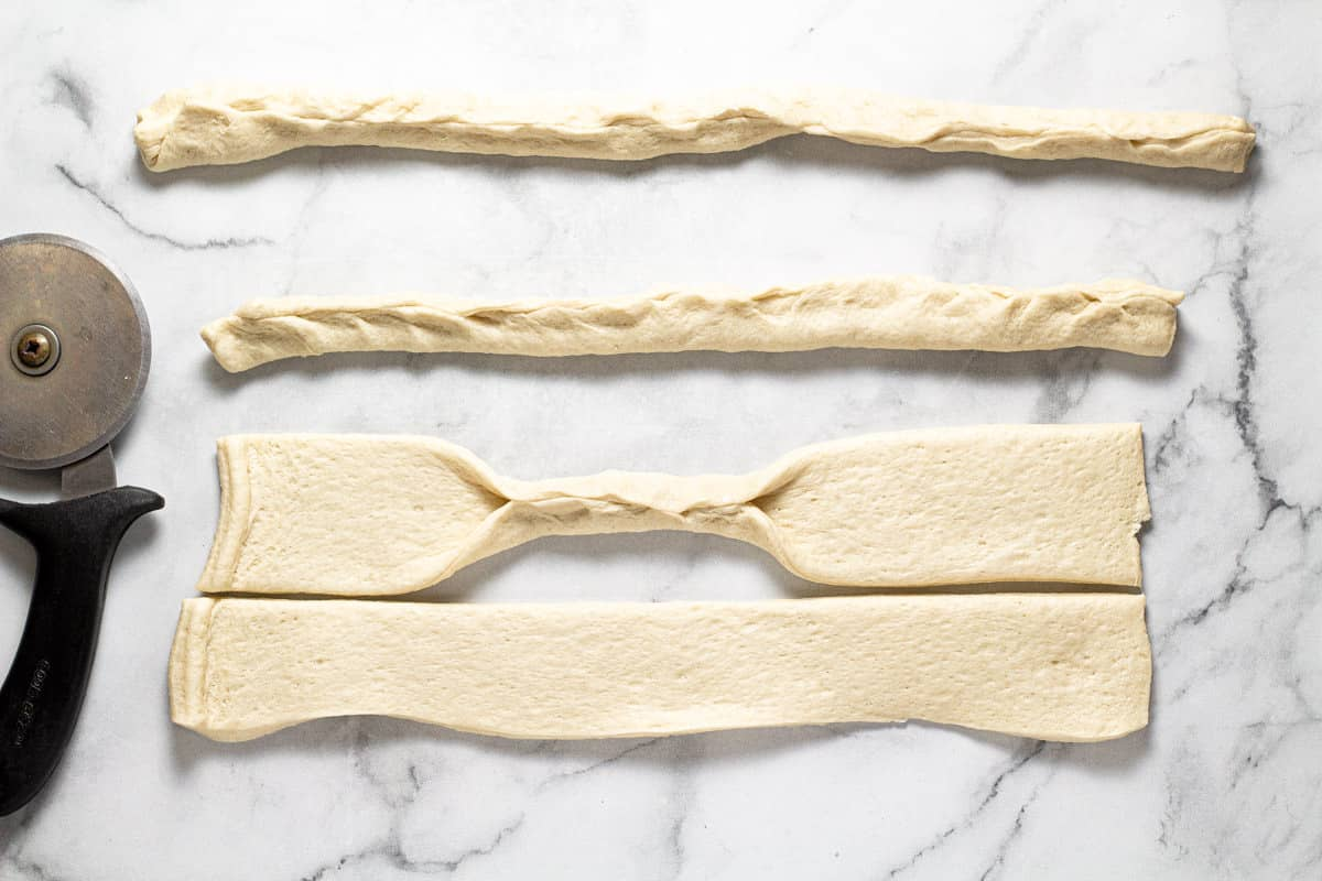 A white marble counter top with pizza dough being pinched into 4 ropes