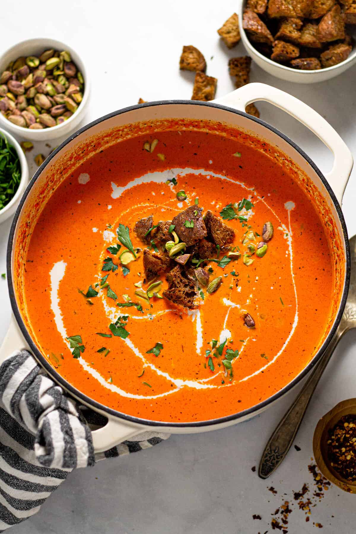 Overhead shot of a pot of roasted red pepper soup garnished with croutons and chopped parsley